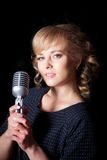 Beautiful girl with a microphone on stage Stock Image