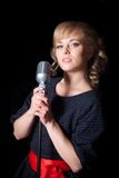 Beautiful girl with a microphone on stage Royalty Free Stock Photography