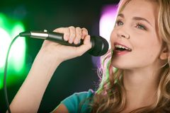 Beautiful girl with microphone standing in bar. Royalty Free Stock Photos