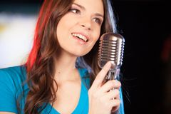Beautiful girl with microphone standing in bar. Stock Images