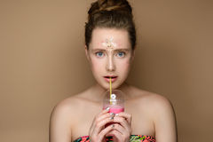 Beautiful girl with milk shake coctail in hand and tinsel makeup. Portrait of young beautiful girl with milk shake coctail in hand and updo on the gold Royalty Free Stock Images