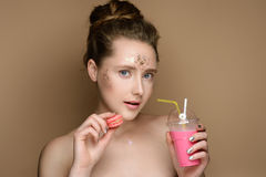 Beautiful girl with milk shake coctail and macaroon in hand and tinsel makeup Stock Image