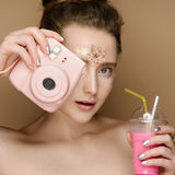 Beautiful girl with milk shake coctail and pink camera in hand and tinsel makeup. Portrait of young beautiful girl with pink milk shake coctail and camera in Royalty Free Stock Photo