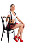 Beautiful girl in mini-skirt. Young pretty woman in white top and red mini skirt sitting on chair Stock Photo