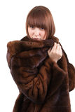 The beautiful girl in a mink fur coat. On a white background Royalty Free Stock Images