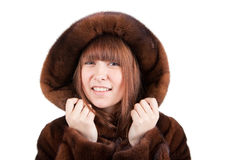 The beautiful girl in a mink fur coat. On a white background Stock Photo