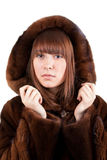 The beautiful girl in a mink fur coat. On a white background Stock Image