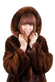 The beautiful girl in a mink fur coat. On a white background Stock Photos