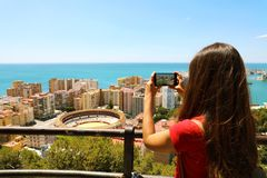 Beautiful girl with mobile phone take picture of Malaga landscape with bullring, Malaga, Spain. stock photography