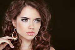 Beautiful girl model with curly long hair and fashion earrings i Stock Photos