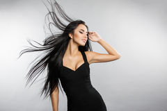 Beautiful girl model with flying the wind hair. A brunette woman in a black dress Stock Photos