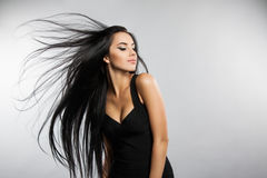 Beautiful girl model with flying the wind hair. A brunette woman in a black dress Stock Image