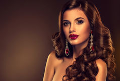 Beautiful girl model with long brown curled hair. With large necklace royalty free stock image