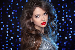 Beautiful girl model with long brown curled hair and red lips ov Royalty Free Stock Photo