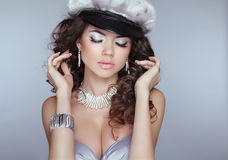 Beautiful girl model with makeup, curly hair and fashion earring Royalty Free Stock Photo