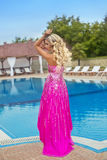 Beautiful girl model in pink fashion dress posing by blue outdoo Stock Photos