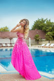 Beautiful girl model in pink fashion dress posing by blue outdoo Royalty Free Stock Image