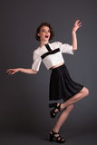 Beautiful girl model posing. Beautiful girl in a black skirt and a white jacket model posing on a black background Pin-up Royalty Free Stock Photography