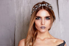 Beautiful girl model in the Studio shooting beauty. Silver makeup, hair in a sloppy spit, silver top. Cold. Beautiful girl model in the Studio shooting beauty royalty free stock photography