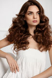 Beautiful Girl Model With Wavy Curly Hairstyle. Brown Hair Color. Hair Style. Beautiful Woman With Healthy Long Wavy Curly Hair And Gorgeous Face Makeup royalty free stock photography