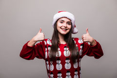 Beautiful girl model wear santa hat and christmas sweater with okey gesture. On grey background Stock Images