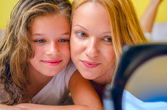Beautiful girl and mom looking into hand  mirror. Smiling mother and daughter relaxing in bed and looking into mirror Royalty Free Stock Photography