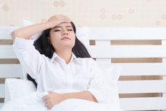 Beautiful girl in the morning, lying on a white bed in a white shirt with headache / insomnia / migraine / stress Royalty Free Stock Photos