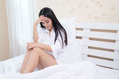 Beautiful girl in the morning, lying on a white bed in a white shirt with headache / insomnia / migraine / stress Stock Images