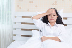Beautiful girl in the morning, lying on a white bed in a white shirt with headache / insomnia / migraine / stress Royalty Free Stock Images