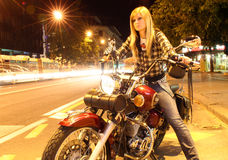 Beautiful girl on a motorcycle in a city (long exposure) Royalty Free Stock Image