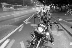 Beautiful girl on a motorcycle in a city (long exposure) Royalty Free Stock Images
