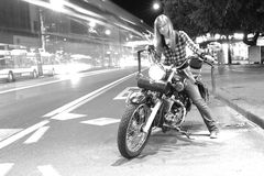 Beautiful girl on a motorcycle in a city (long exposure) Stock Photos