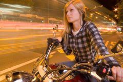 Beautiful girl on a motorcycle in a city (long exposure) Stock Images