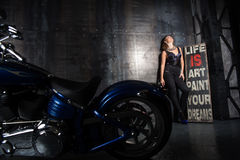 Beautiful girl and a motorcycle. Girl dressed in a black tight-fitting clothes. and standing at the wall. foreground expensive chrome plating Harley Davidson Royalty Free Stock Photo