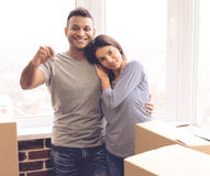 Beautiful girl moving. Beautiful couple is hugging, looking at camera and smiling while standing near the boxes ready to move. Guy is holding keys Royalty Free Stock Image