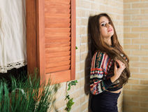 Beautiful girl in a multicolored knitted sweater stands near the brick wall. Near the window. Royalty Free Stock Photos