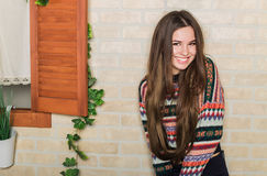 Beautiful girl in a multicolored knitted sweater stands near the brick wall. Near the window. Royalty Free Stock Image