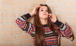 Beautiful girl in a multicolored knitted sweater stands near the brick wall. Near the window. Royalty Free Stock Photography