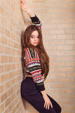 Beautiful girl in a multicolored knitted sweater stands near the brick wall. Near the window. Stock Photo