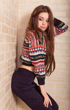 Beautiful girl in a multicolored knitted sweater stands near the brick wall. Near the window. Royalty Free Stock Images