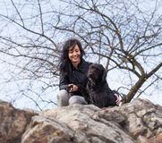 Beautiful girl with mutt black dog on mountains Stock Photo