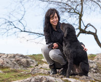 Beautiful girl with mutt black dog on mountains Royalty Free Stock Photography