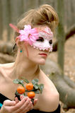 Beautiful girl in a mysterious mask in the forest with a decorative tangerine tree Royalty Free Stock Photo