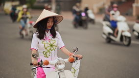 Beautiful girl in national dress Ao Dai and Non La cap sits on a motorbike stock footage