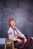 A beautiful girl in National Ukrainian Costume. captured in studio. Embroidery and jacket. wreath. circlet of flowers. red lips Stock Photo