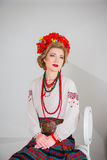 A beautiful girl in National Ukrainian Costume. captured in studio. Embroidery and jacket. wreath. circlet of flowers. red lips Stock Images