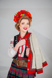 A beautiful girl in National Ukrainian Costume. captured in studio. Embroidery and jacket. wreath. circlet of flowers. red lips. A beautiful girl in National Stock Photo