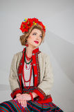 A beautiful girl in National Ukrainian Costume. captured in studio. Embroidery and jacket. wreath. circlet of flowers. red lips. A beautiful girl in National Royalty Free Stock Image