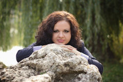 The beautiful girl near a big stone. The beautiful girl has a walks in park near a big stone Stock Photography