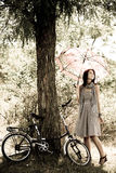 Beautiful girl near bike.. Beautiful girl near bike and tree at rest in forest. Photo in retro style Royalty Free Stock Images